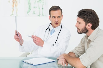 Male doctor explaining spine xray to patient