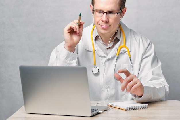 Male doctor explains treatment recommendations via video chat on laptop.
