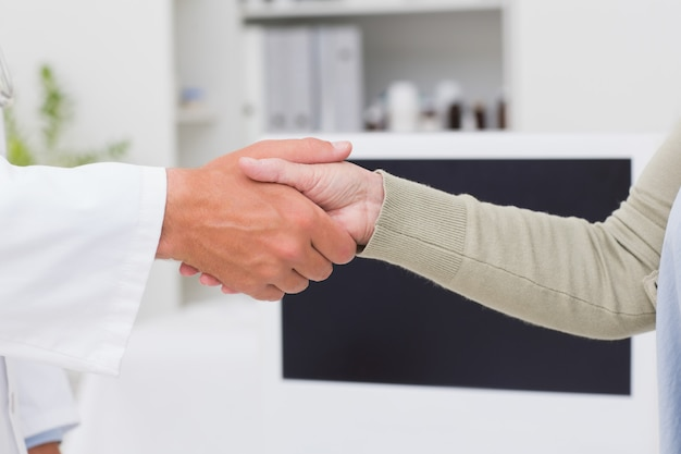Male doctor and female patient shaking hands