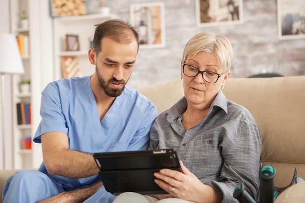 백인 노인 여성이 요양원에서 태블릿 컴퓨터를 사용하도록 돕는 남성 의사.