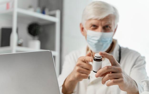 Medico maschio alla sua scrivania con qualche medicina