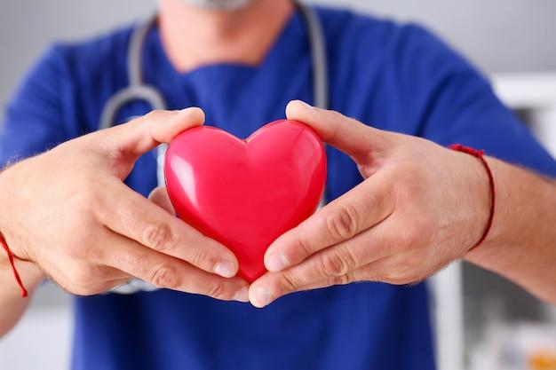 男性医師が腕の中で保持する赤いハート
