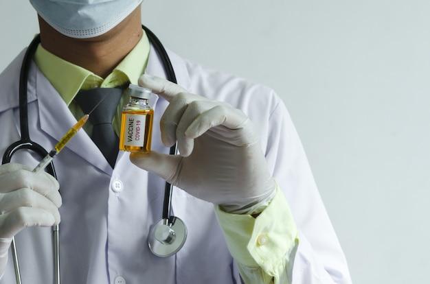 Covid-19 백신 약 또는 코로나 바이러스 백신 및 주사기 한 병을 들고 남성 의사