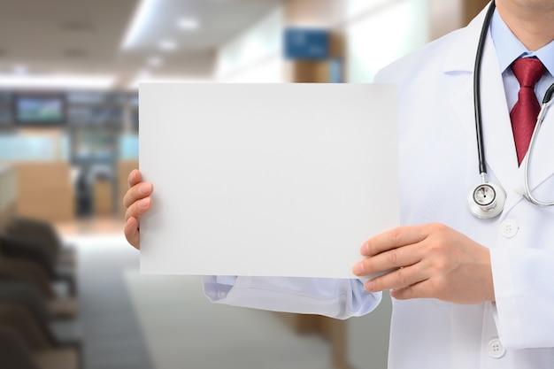 Мужской доктор, держа доску объявлений в больнице.