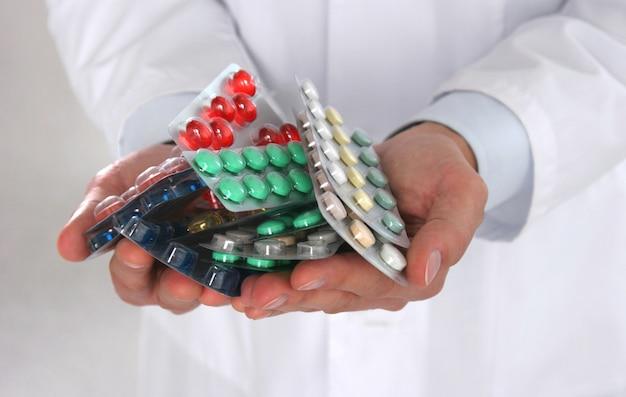 Мужской доктор, держа стопку разных таблеток