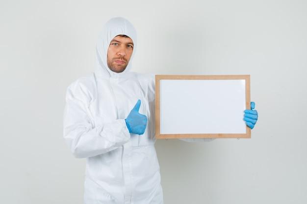 Medico maschio che tiene cornice vuota con il pollice in su in tuta protettiva
