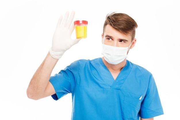 白い背景で隔離の尿サンプルのボトルを保持している男性医師
