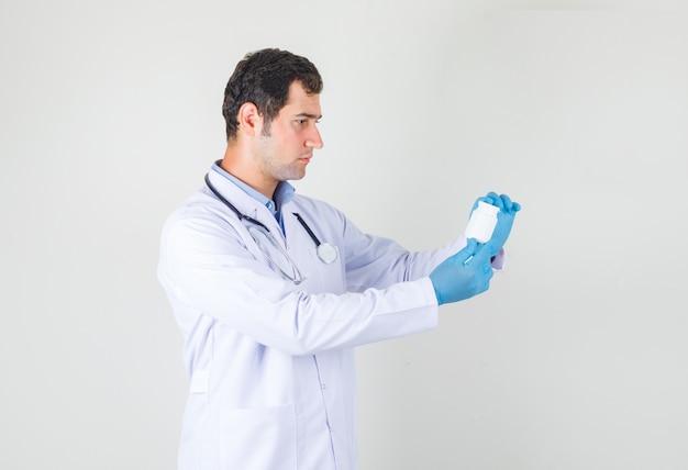 Medico maschio che tiene una bottiglia di pillole in camice bianco, guanti e che sembra seria