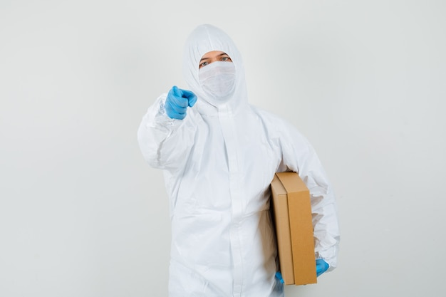 段ボール箱を保持し、防護服でカメラを指して男性医師