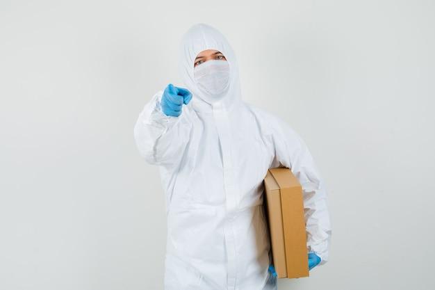 Medico maschio che tiene una scatola di cartone, che punta alla telecamera in tuta protettiva