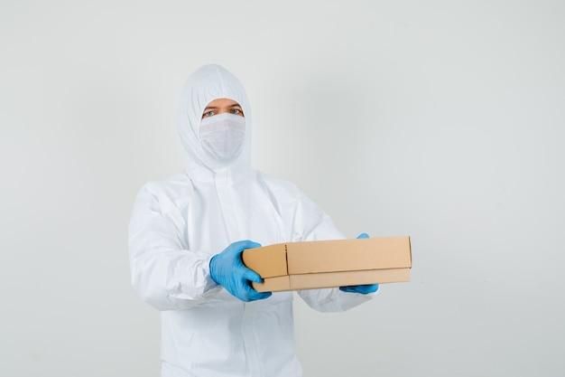 Medico maschio che tiene la scatola di cartone in tuta protettiva