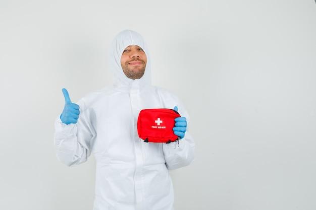 Врач-мужчина держит аптечку, показывая большой палец вверх в защитном костюме
