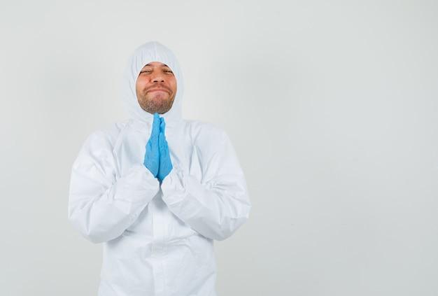 Medico maschio che tengono le mani nel gesto di preghiera in tuta protettiva