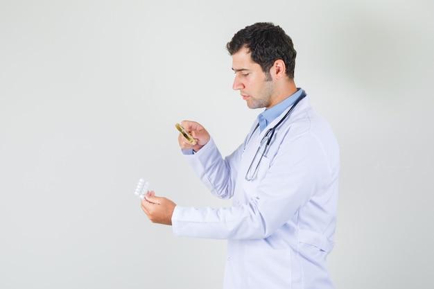 Врач-мужчина держит увеличительное стекло над таблетками в белом халате и выглядит серьезно. .