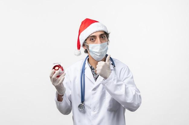 Medico maschio che tiene il virus del giocattolo dell'albero di capodanno covid