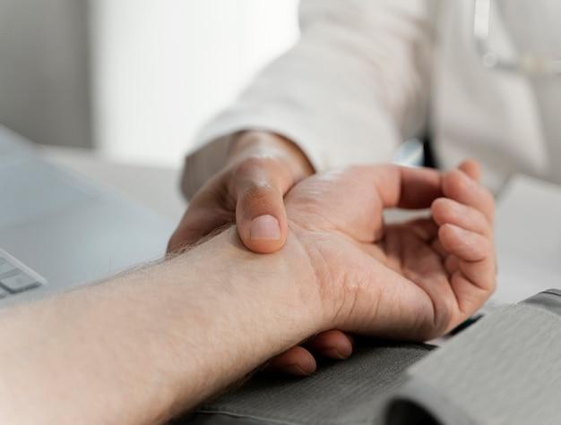 患者の手を握って男性医師