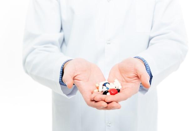 白い背景で隔離の丸薬を保持している男性医師