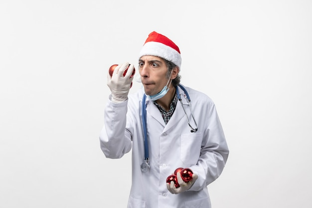 プラスチックのおもちゃの机を持っている男性医師は、ウイルスの健康感情をcovid