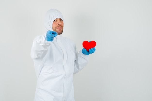 Male doctor holding red heart, pointing at camera in protective suit
