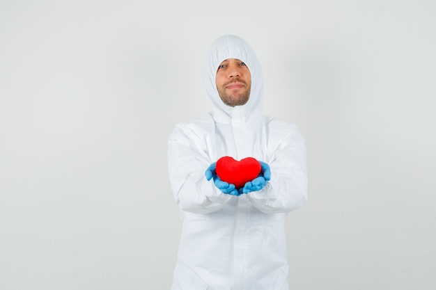 Male doctor holding red heart in protective suit
