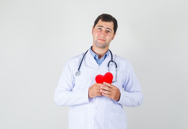 Male doctor holding red heart in white coat and looking hopeful