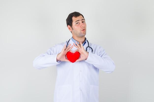 Medico maschio che tiene cuore rosso in camice bianco