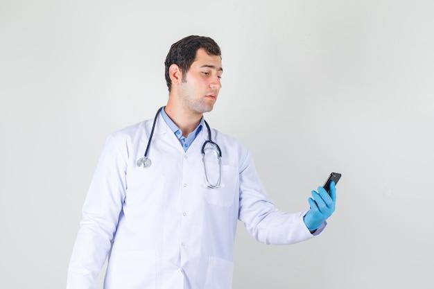 Мужчина-врач держит смартфон в белом халате, перчатках и серьезно выглядит