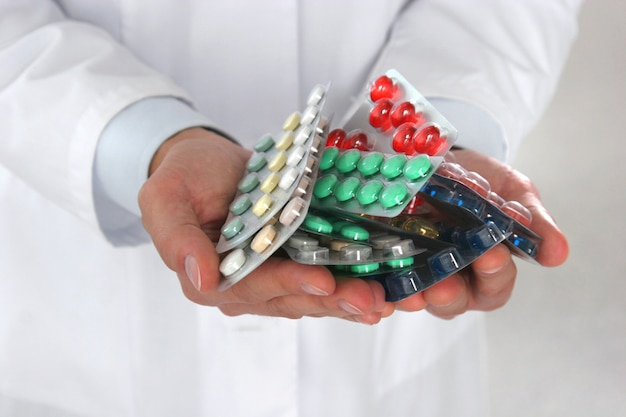 Male doctor holding a stack of many different pills.