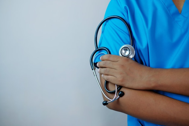 Male doctor holding stethoscope with arm crossed