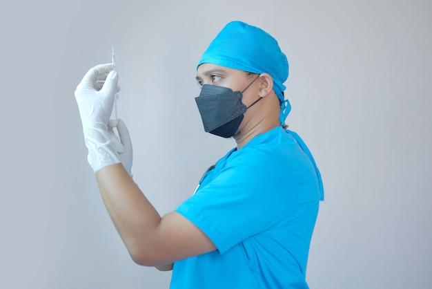 手に注射器を保持している男性医師