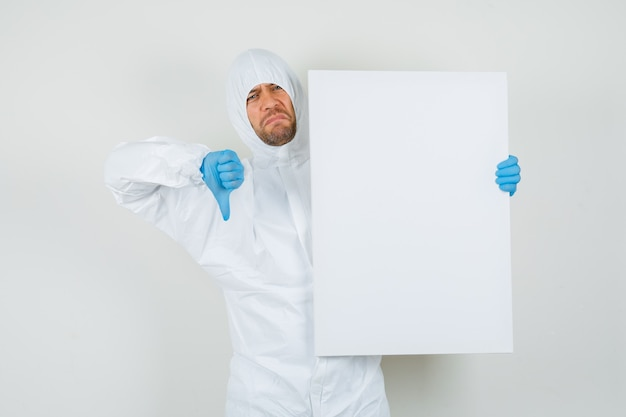 Male doctor holding white board with thumb down in protective suit