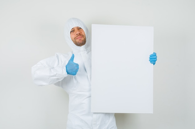 Male doctor holding white board with thumb up in protective suit