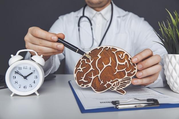 나무 뇌를 들고 남성 의사입니다. 조기 진단 개념의 중요성.