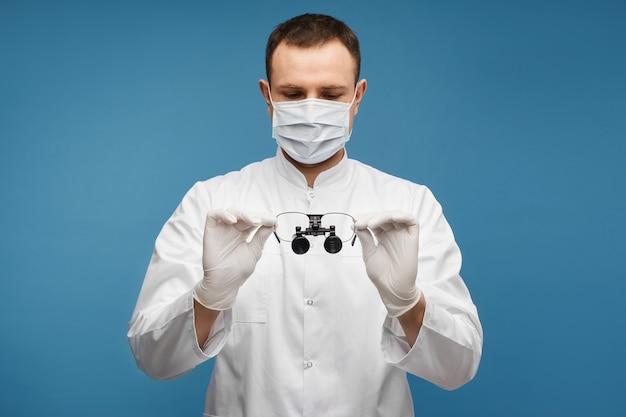 サージカルマスクと保護手袋を着用した男性医師は、コピースペースで青い背景で隔離された両眼ルーペを手に保ちます