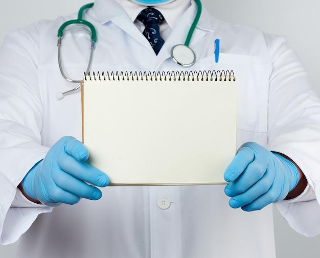 白いコートと医療の青い手袋の男性医師が空白の白いシートでノートを保持します