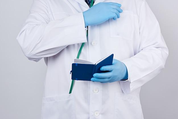 開いている青い紙のノートを保持しているボタンを持つ白衣の男性医師