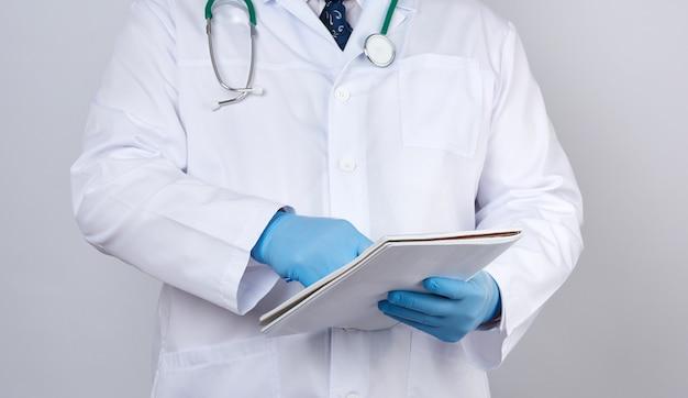 彼の手で紙のノートを保持しているボタンを持つ白衣の男性医師