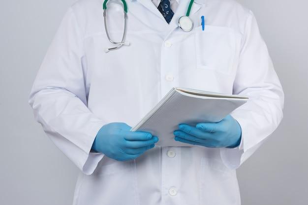 紙のノートを保持しているボタンを持つ白衣の男性医師