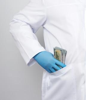 白の医療用コートと青いラテックス手袋の男性医師が彼のコートポケットに米ドルのスタックを入れます
