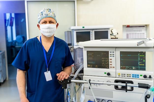 Врач-мужчина в синей форме носит в руках медицинскую маску. светлый фон. медицинский работник в офисе.