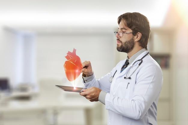 タブレットから出てくる仮想の心臓を見ている彼のオフィスの男性医師