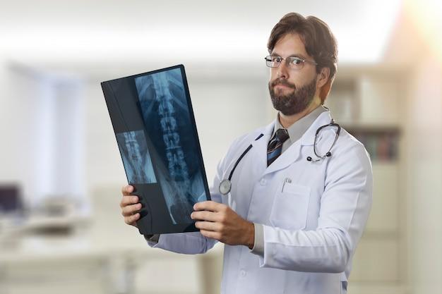 Врач-мужчина в своем кабинете, глядя на рентген