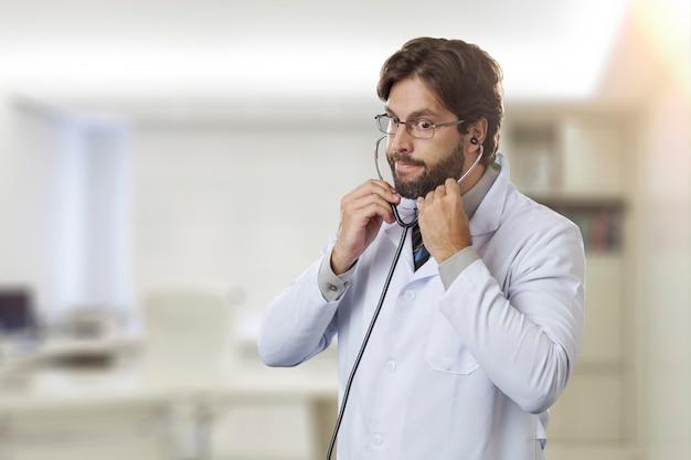 聴診器を使用して彼のオフィスの男性医師。