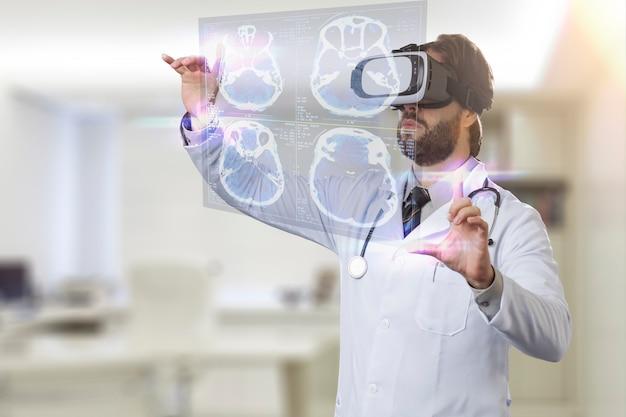 Врач-мужчина в своем кабинете, используя очки виртуальной реальности, смотрит на виртуальный экран