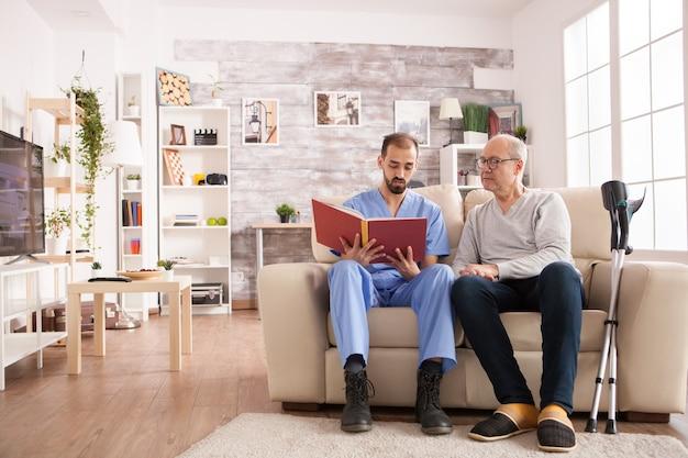 요양원에 있는 남자 의사가 알츠하이머를 들고 노인에게 책을 읽고 있습니다.