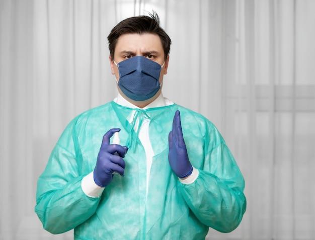 保護具の男性医師が自宅で消毒スプレーを使用する方法を示しています