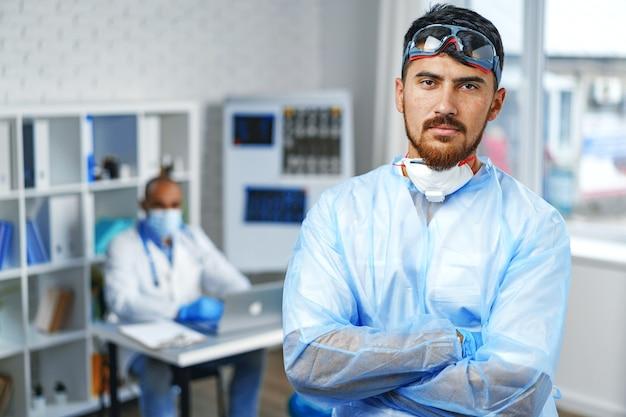 병원 캐비닛에 서 보호 의료 가운에 남성 의사 초상화