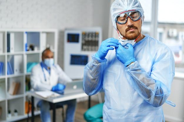 Мужчина-врач в защитном медицинском халате, стоящий в больничном шкафу, портрет