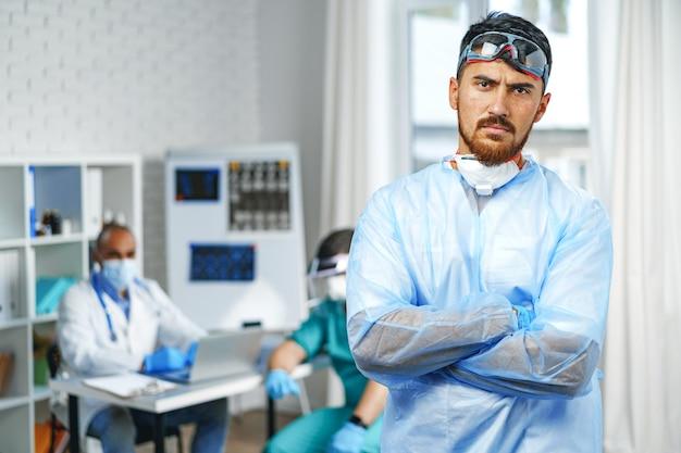 病院のキャビネットに立っている保護医療用ガウンの男性医師