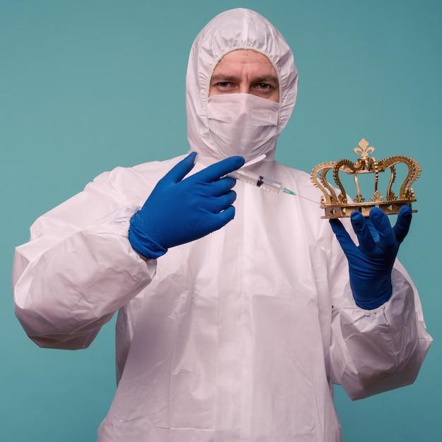 보호 작업복과 마스크를 쓴 남성 의사가 왕관에 주사를 맞 춥니 다.